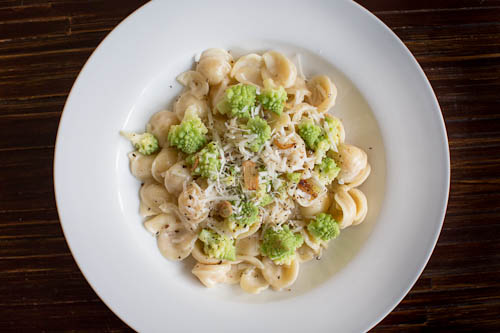 INGREDIENTS   1 head of romanesco  1 clove garlic  4 ounces Pecorino Romano cheese, 2 ounces finely grated and 2 ounces coarsely grated (about 1 cup of each)  2 ounces Parmigiano Reggiano cheese, finely grated (about 1 cup)  1 pound orecchiette pasta  2 tablespoons heavy cream  1 tablespoon + 2 teaspoons extra-virgin olive oil  1 1/2teaspoons finely ground black pepper  Kosher salt to taste      INSTRUCTIONS   Prep the romanesco by removing the exterior leaves and core, and separating it into bite-sized florets. Wash the florets and then blanch them in a large pot of boiling, salted water until they just turn tender (about 3 minutes). Shock them in an ice bath or very cold water to stop the cooking. Set aside.  Bring a large pot of salted water to boil, and add the pasta. Cook until al dente, giving it a stir every once in awhile to keep the pasta from sticking together.  Place the finely grated Pecorino and Parmigiano in a medium bowl, this will be made into a sauce. The coarsely grated Pecorino will be used for garnishing at the end and can be placed in a small serving bowl.  Slice the garlic as thin as you can and sauté in 1 tablespoon of olive oil until lightly toasted. The garlic slices will brown quickly so be careful not to let them burn. Add the romanesco florets and a pinch of salt, and sauté briefly, coating them in the olive oil. Set aside until the pasta is done cooking.  Drain the pasta, reserving 1 ½ cups of the cooking water. Return the pasta to the empty pot.  Slowly whisk 1 cup reserved pasta cooking water into the finely grated Pecorino and Parmigiano until smooth. Whisk in cream, 2 teaspoons olive oil, and black pepper. Gradually pour cheese mixture over pasta, tossing to coat.  Let pasta rest 1 to 2 minutes, tossing frequently. The sauce will thicken a bit as it sets. If it is too thick, add more of the reserved pasta water. Toss in the romanesco. Salt to taste. Top with coarsely grated Pecorino and enjoy immediately!