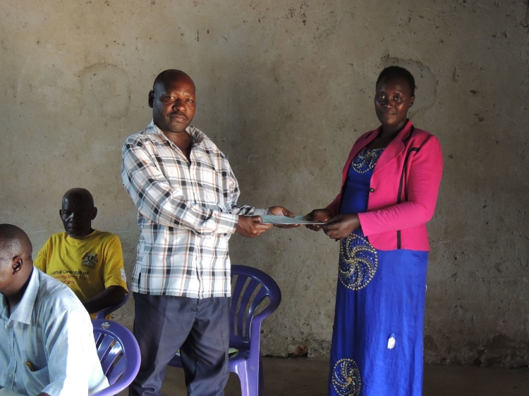 Photo: Peninah handing over the Health and Livelihood survey to the Chairperson of Nalutuntu Sub-County, Kamulegeya Peterson