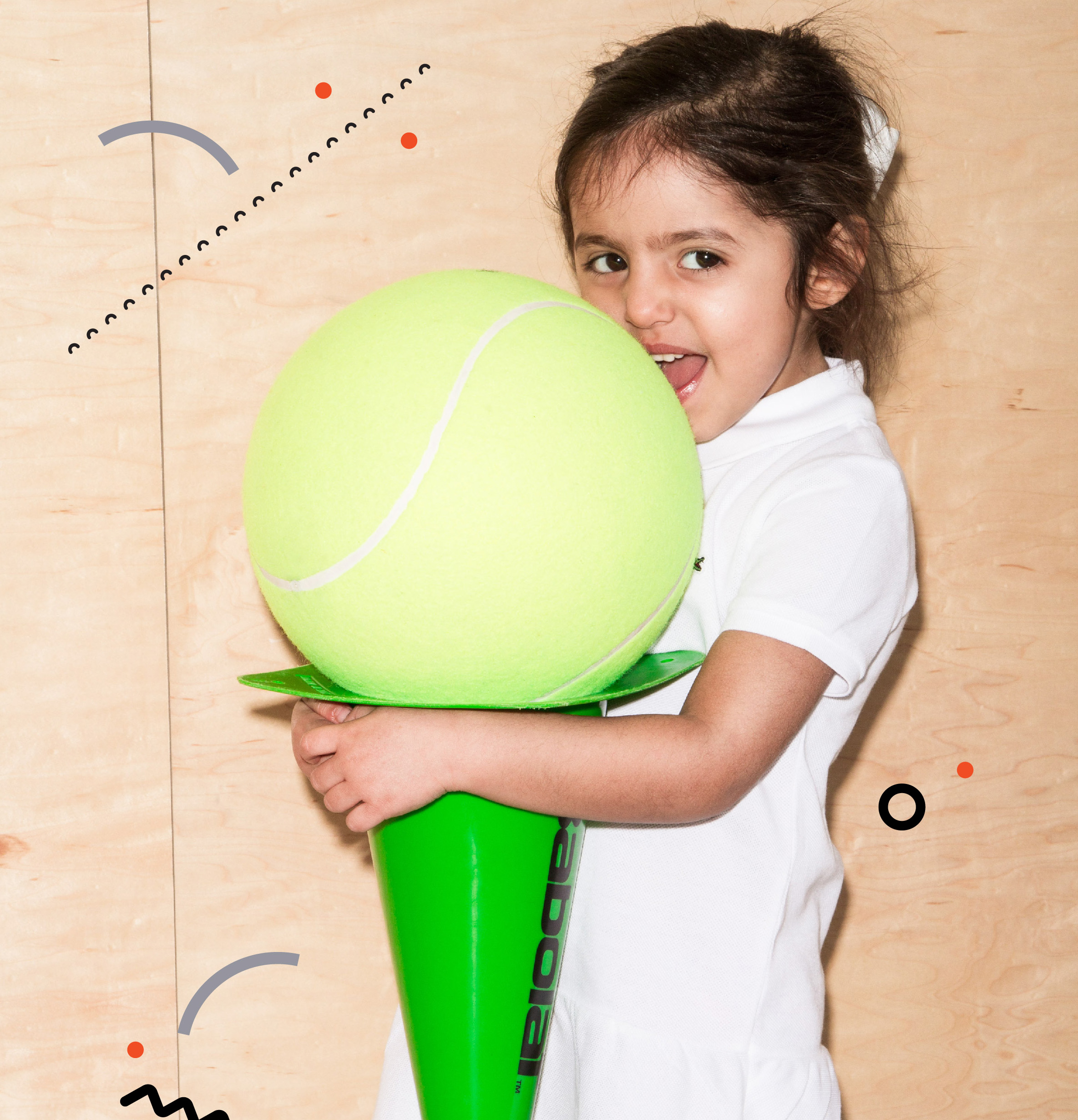 Little girl with giant tennis ball and cone
