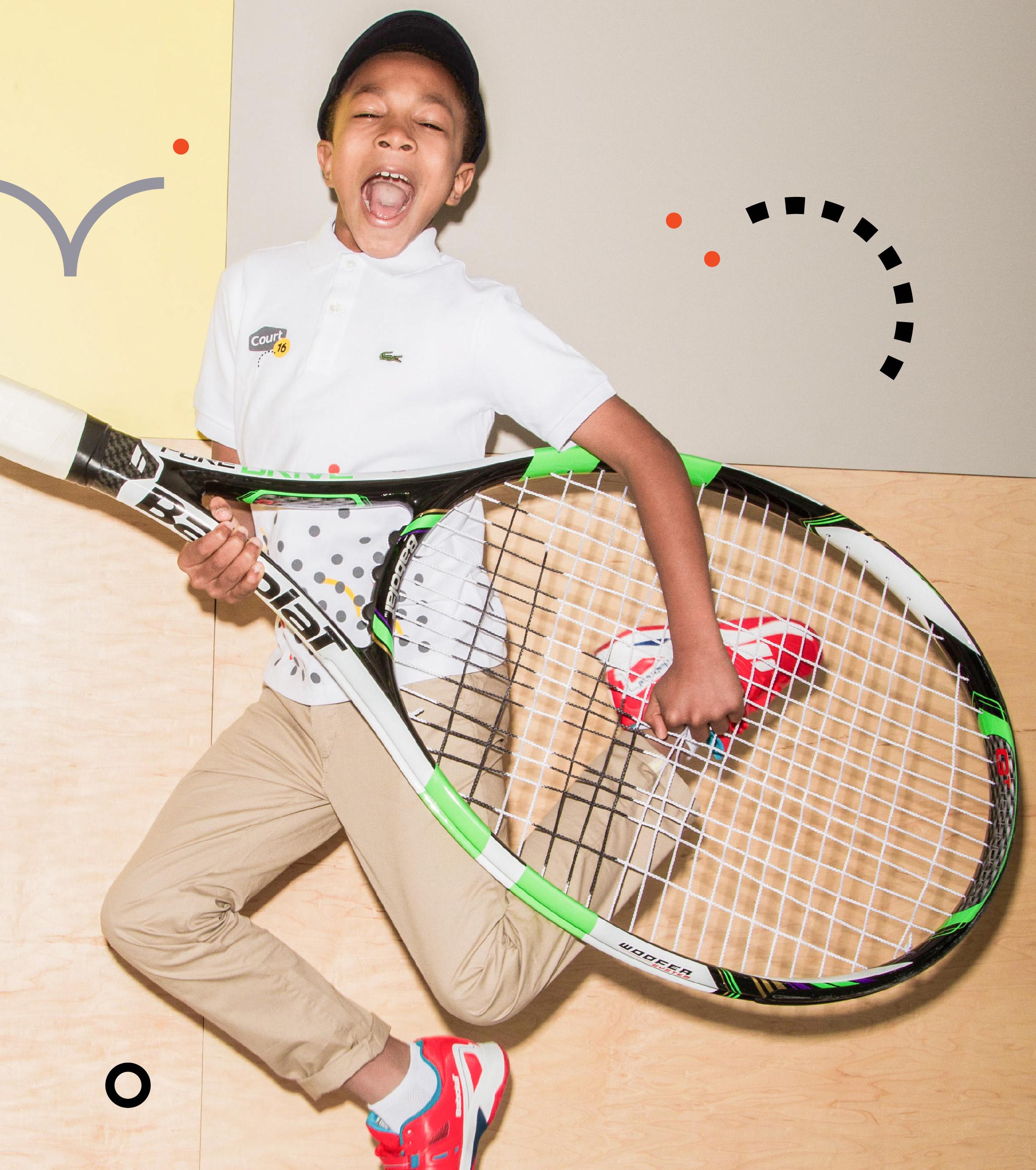 Boy using giant racket to preform guitar solo
