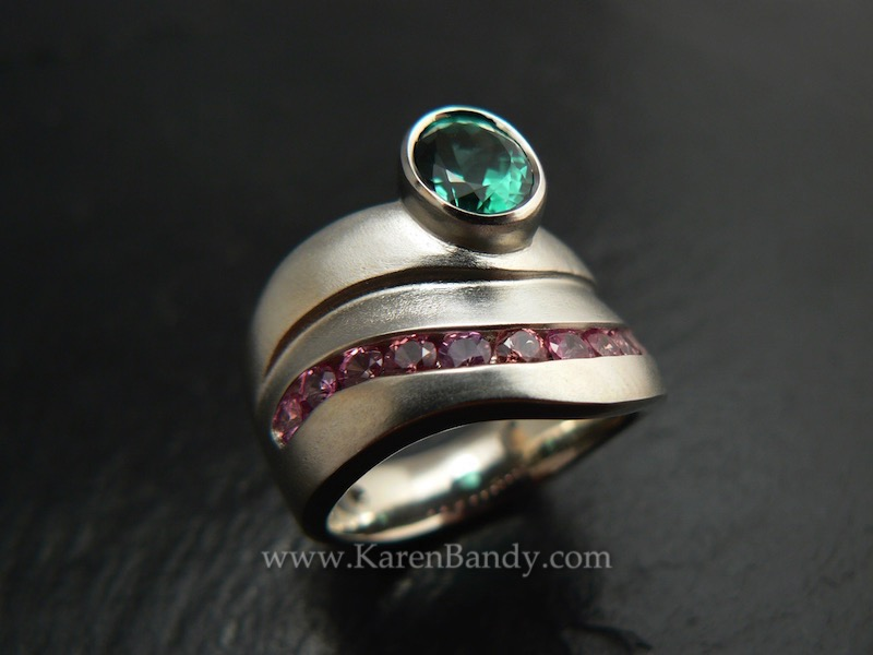 Custom made, one-of-a-kind ring with natural color, fair trade padparadscha sapphires and a mint green tourmaline in 14k white gold. Bead-blast finish.