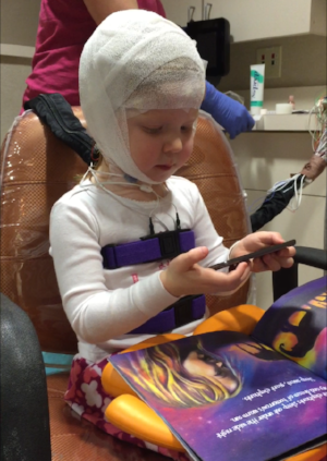 A 2-year old is engrossed by SpellBound and oblivious to sleep study prep.