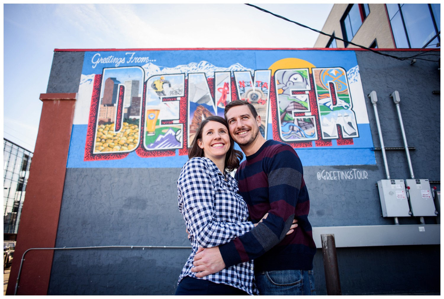 engaged couple smile in front of Denver sign