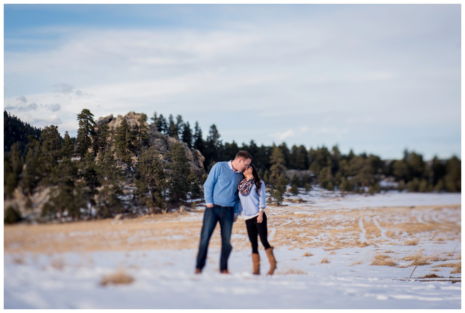 tilt shift photo of engaged couple kissing in Evergreen