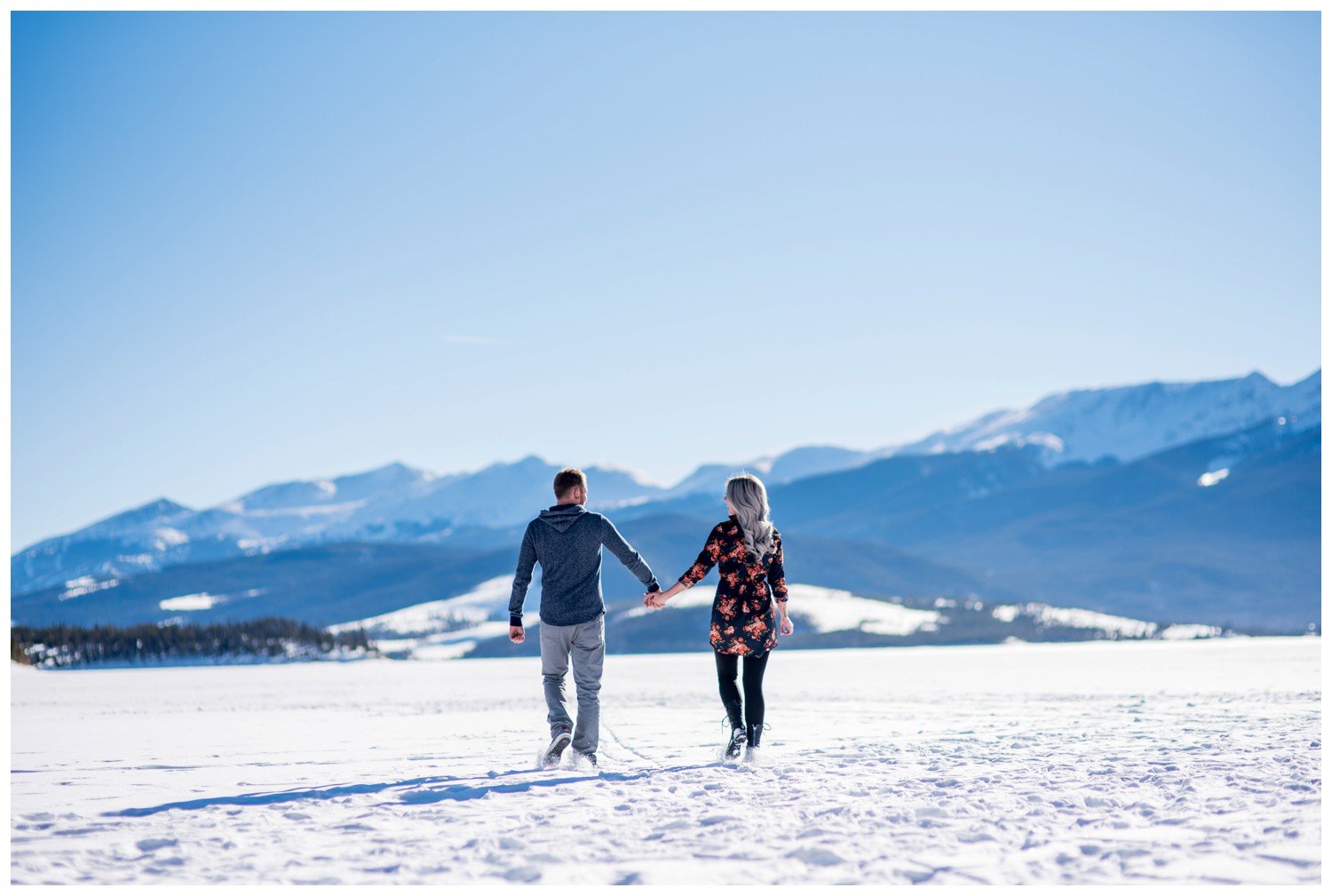 couple holds hands walking on Lake Dillon