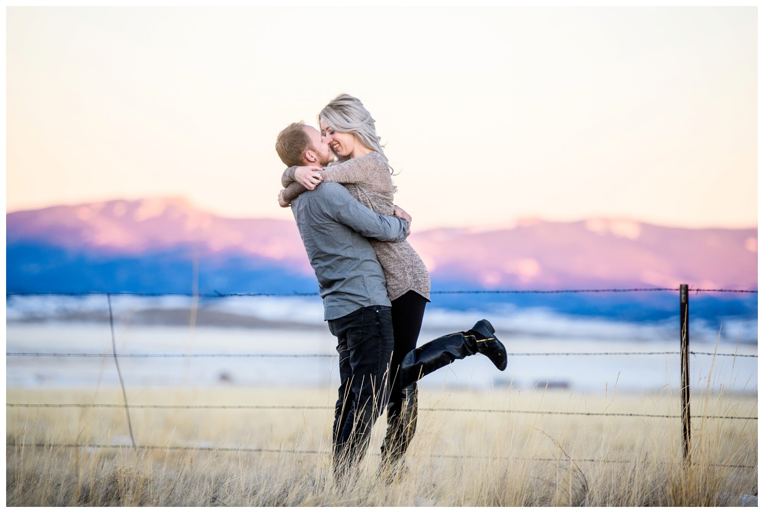 guy lifts girl in front of colorado mountain sunset
