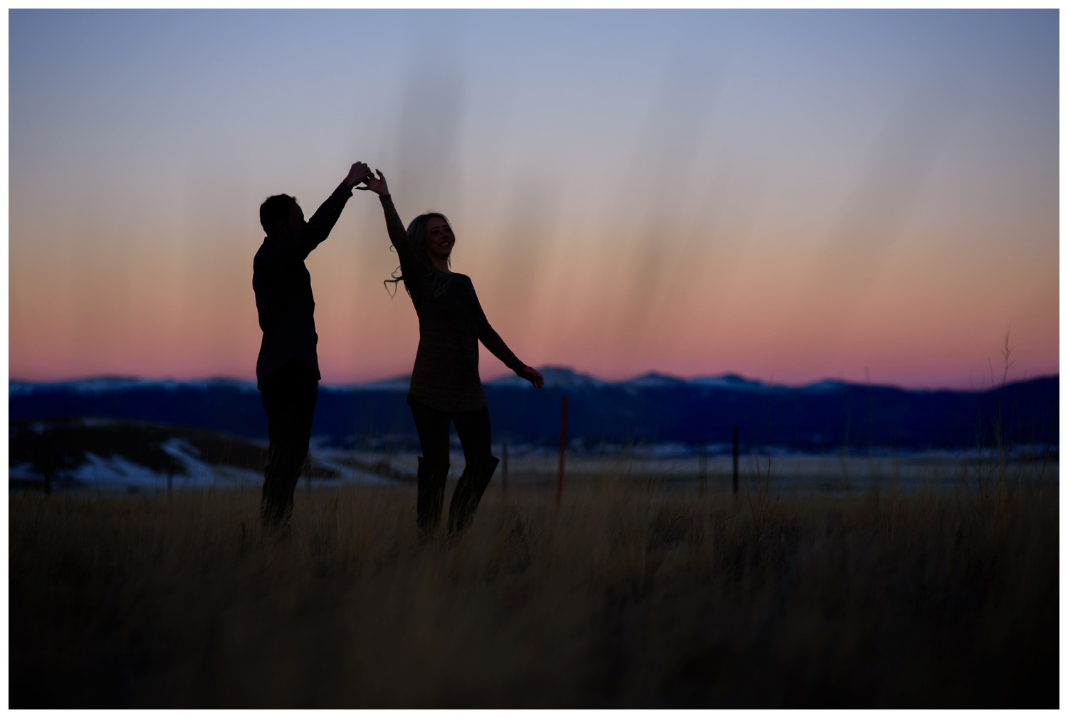 couple dances in field in silhouette sunset photo