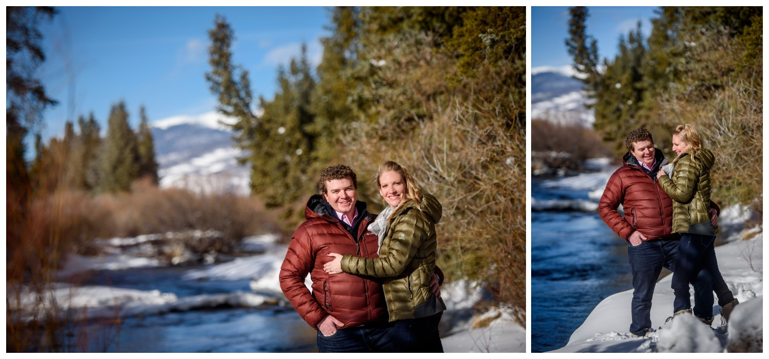 couple laughs standing near river in colorado engagement photo