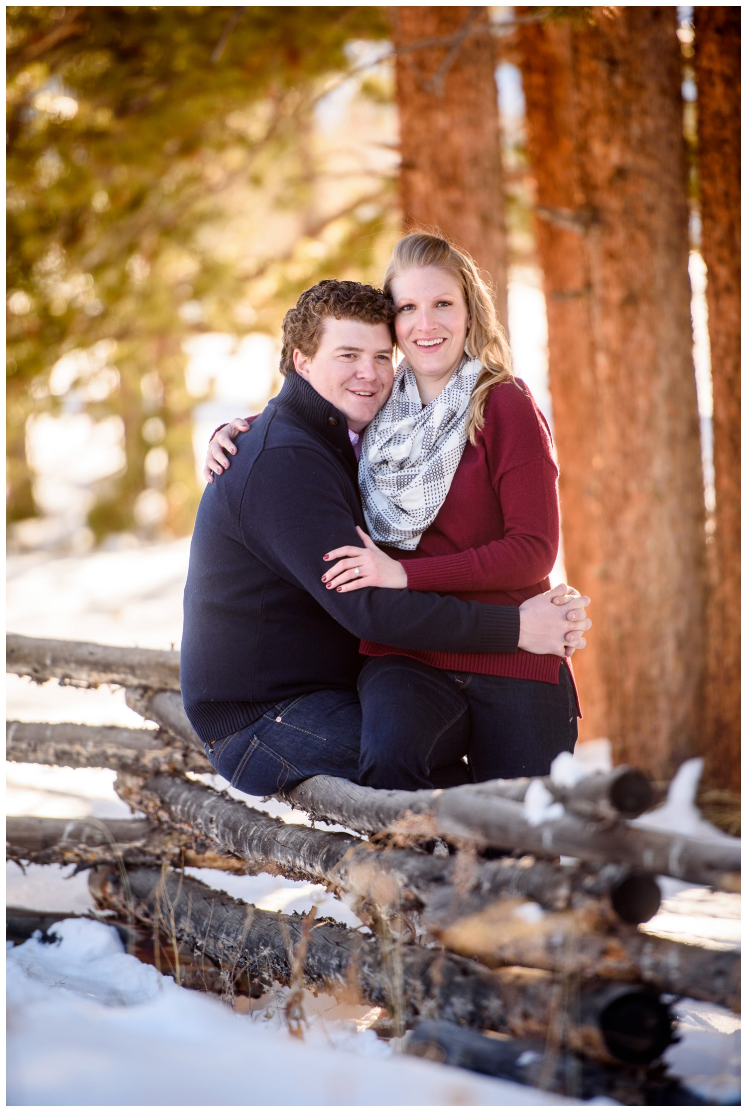 engaged couple sits on wooden fence in mountains