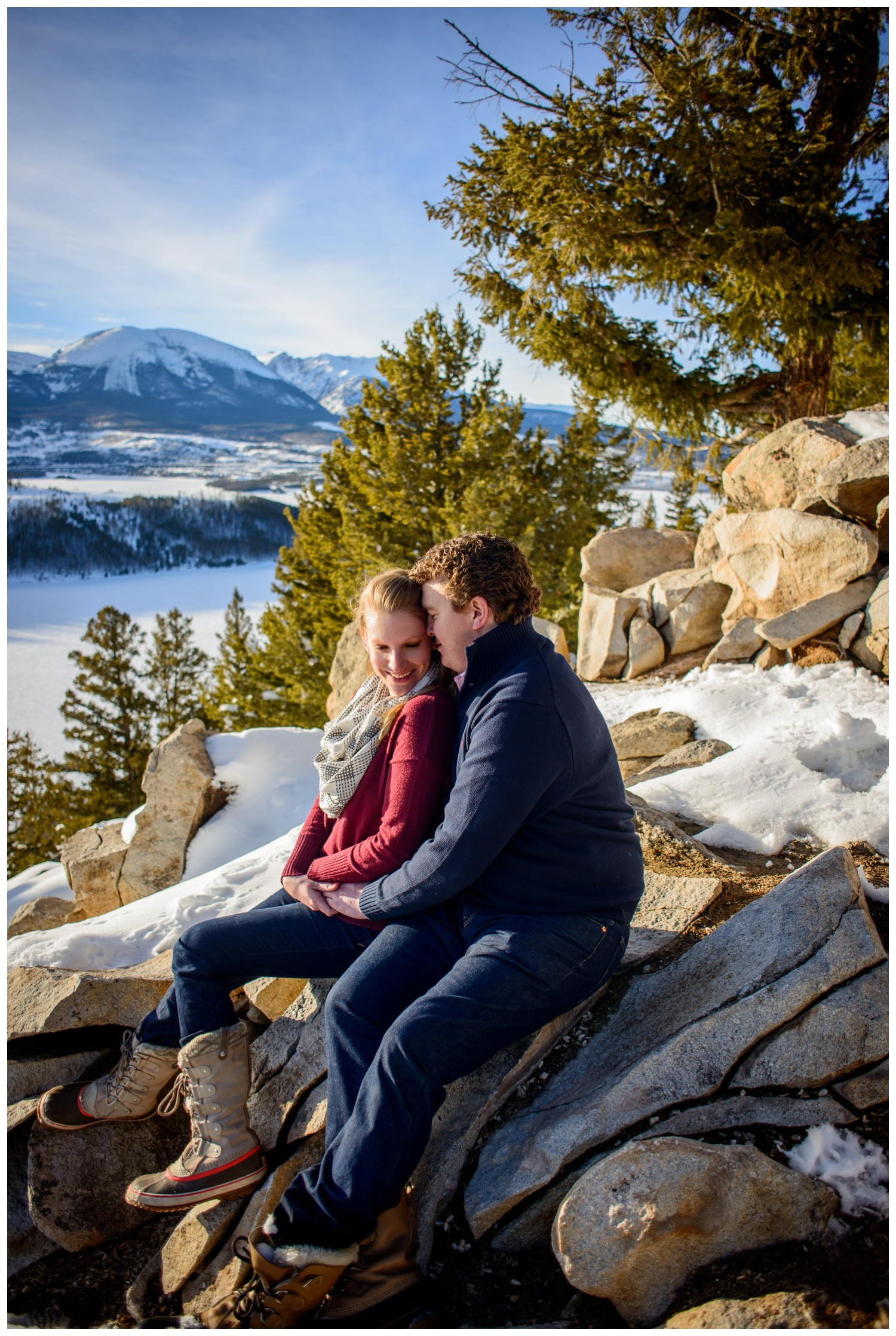 engagement photo of couple sitting in mountain ledge at Sapphire Point