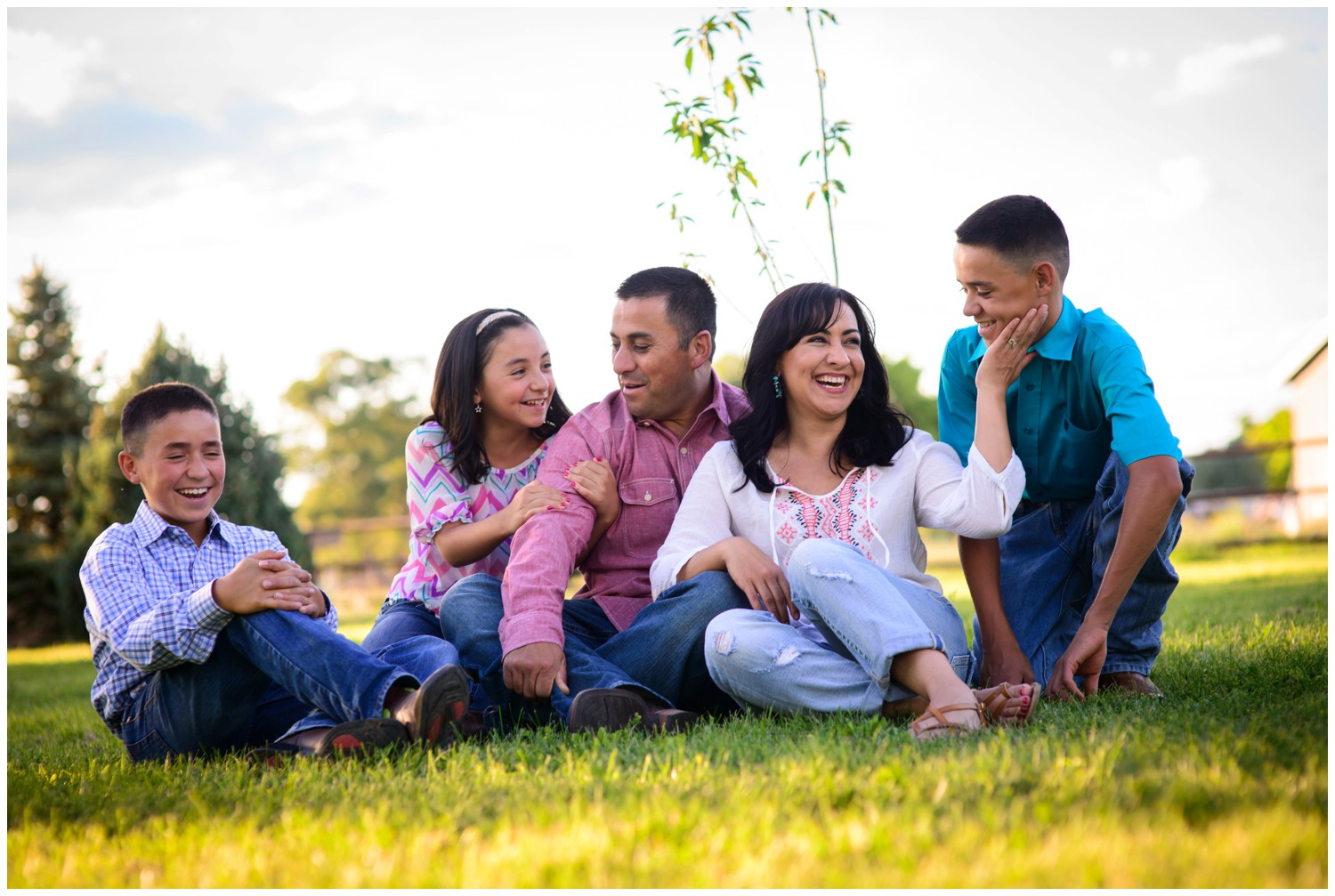 laughing family sitting in grass