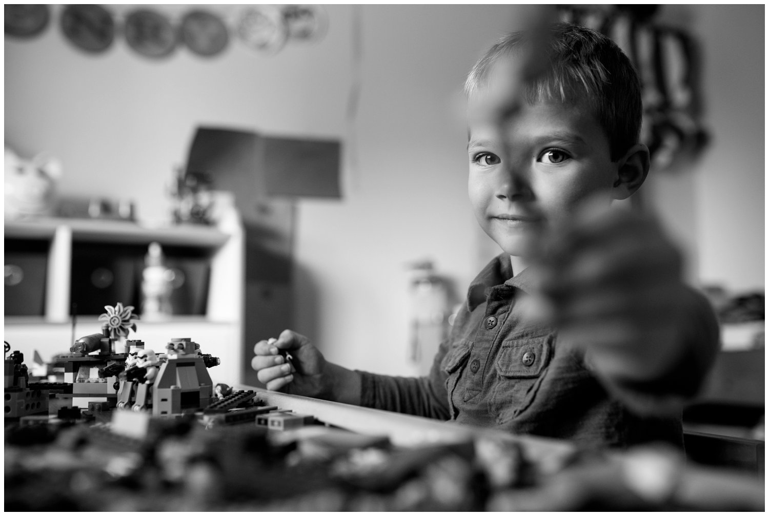 little boy plays legos in room