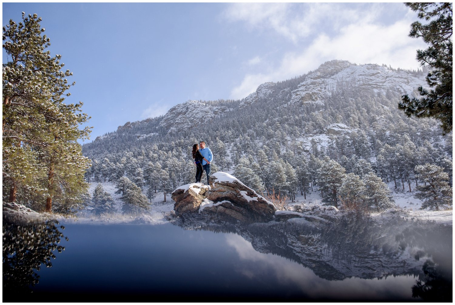 couple stands on colorado mountain ledge in winter