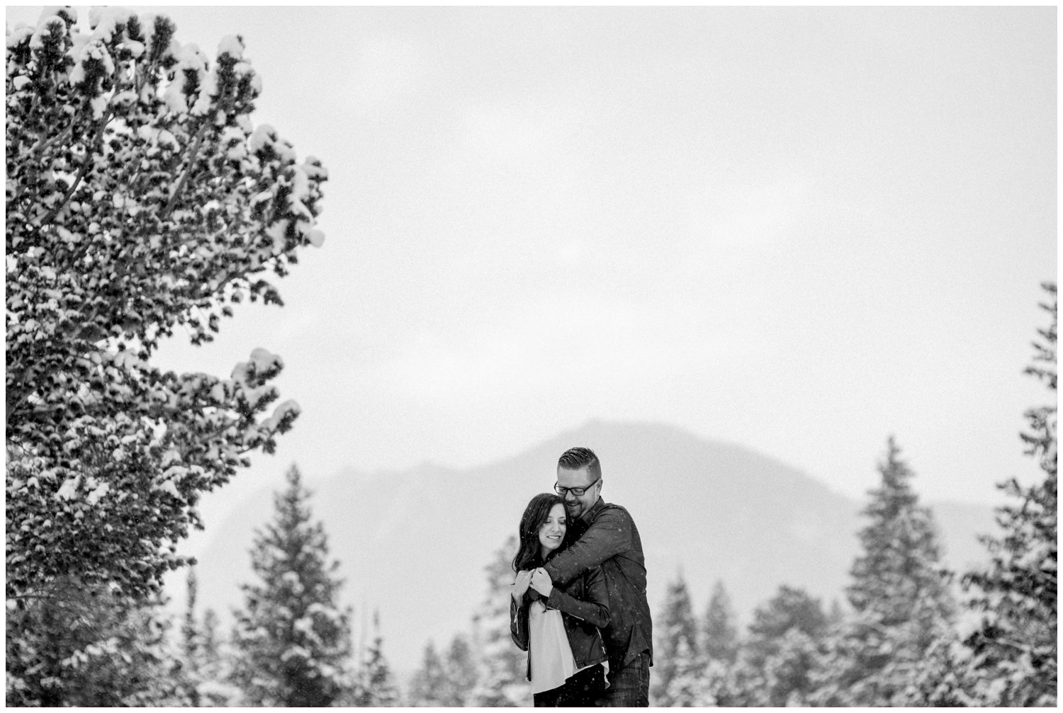 black and white photo of couple on snowy mountain