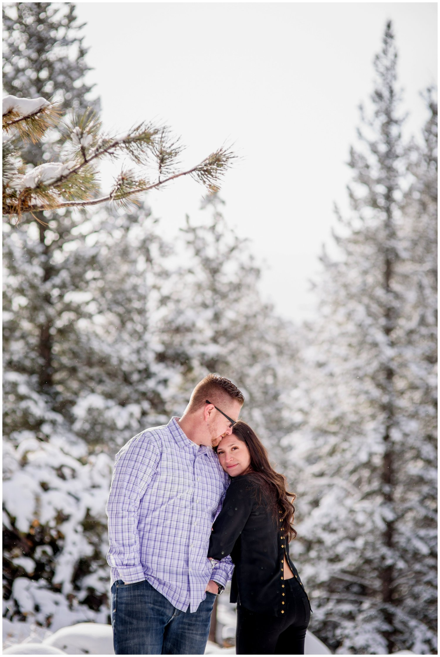 guy kisses girls head in sunny snowy engagement photo