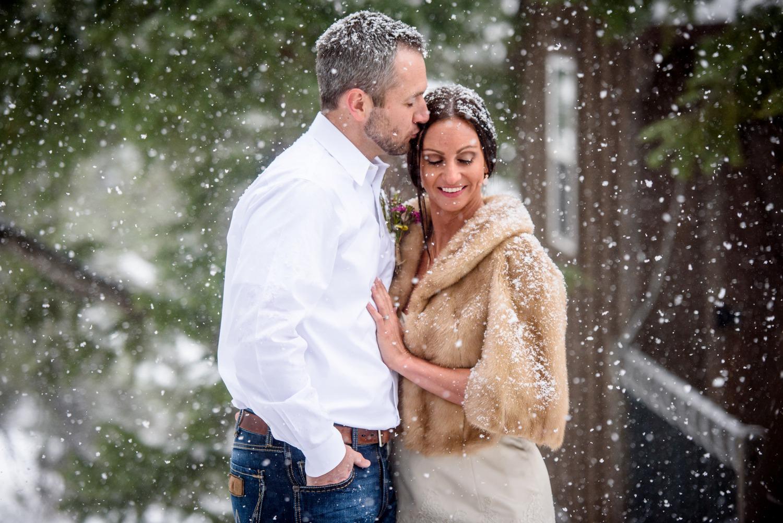 groom kisses bride in falling snow