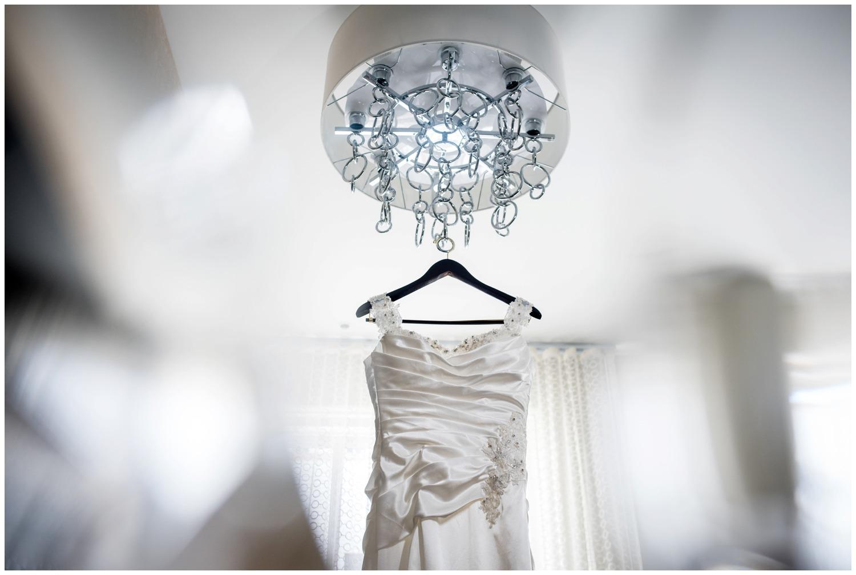 wedding dress hangs from chandelier