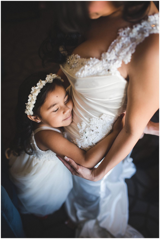 flowergirl hugs bride while getting ready in Denver