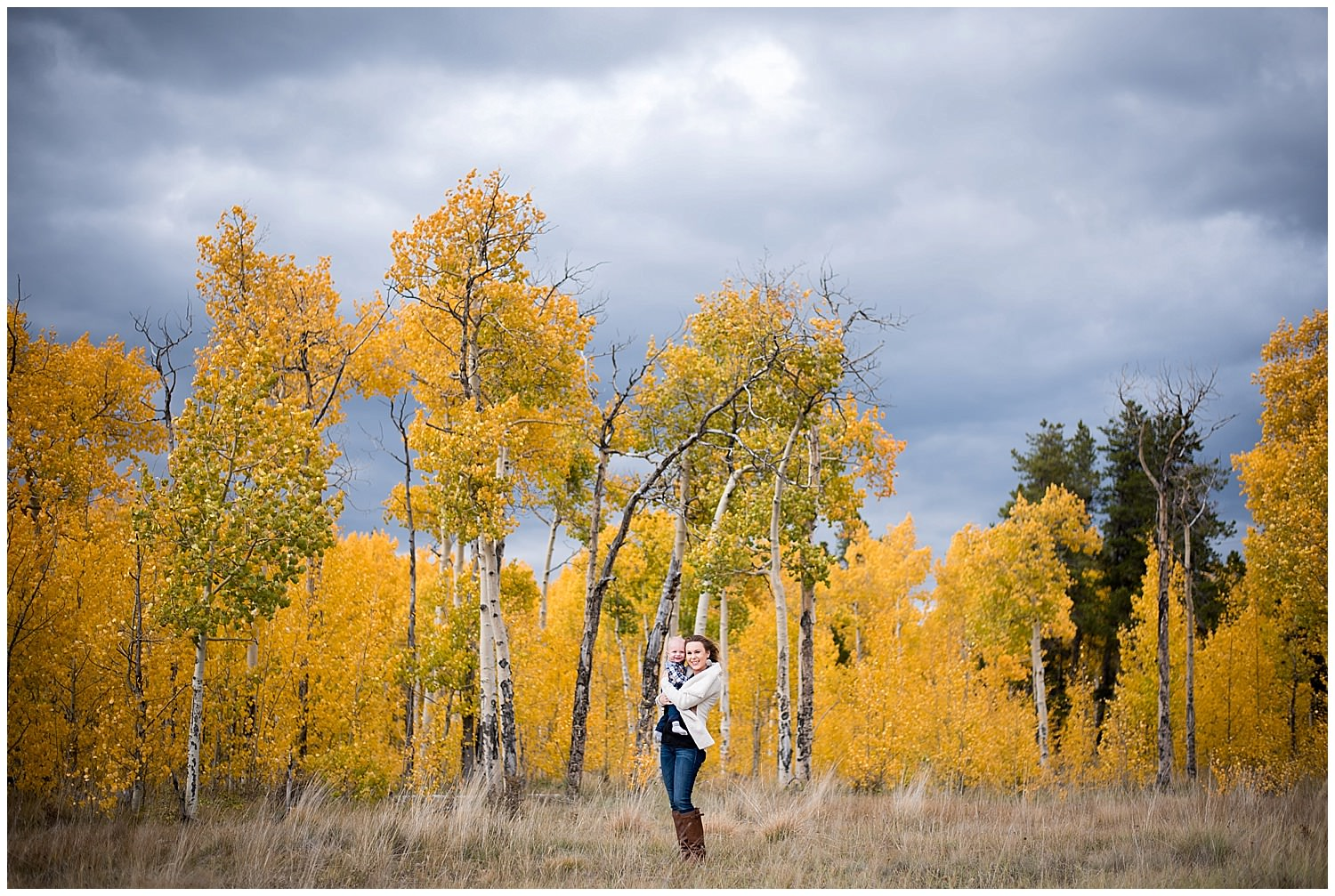mom and baby photo with cool clouds and aspens