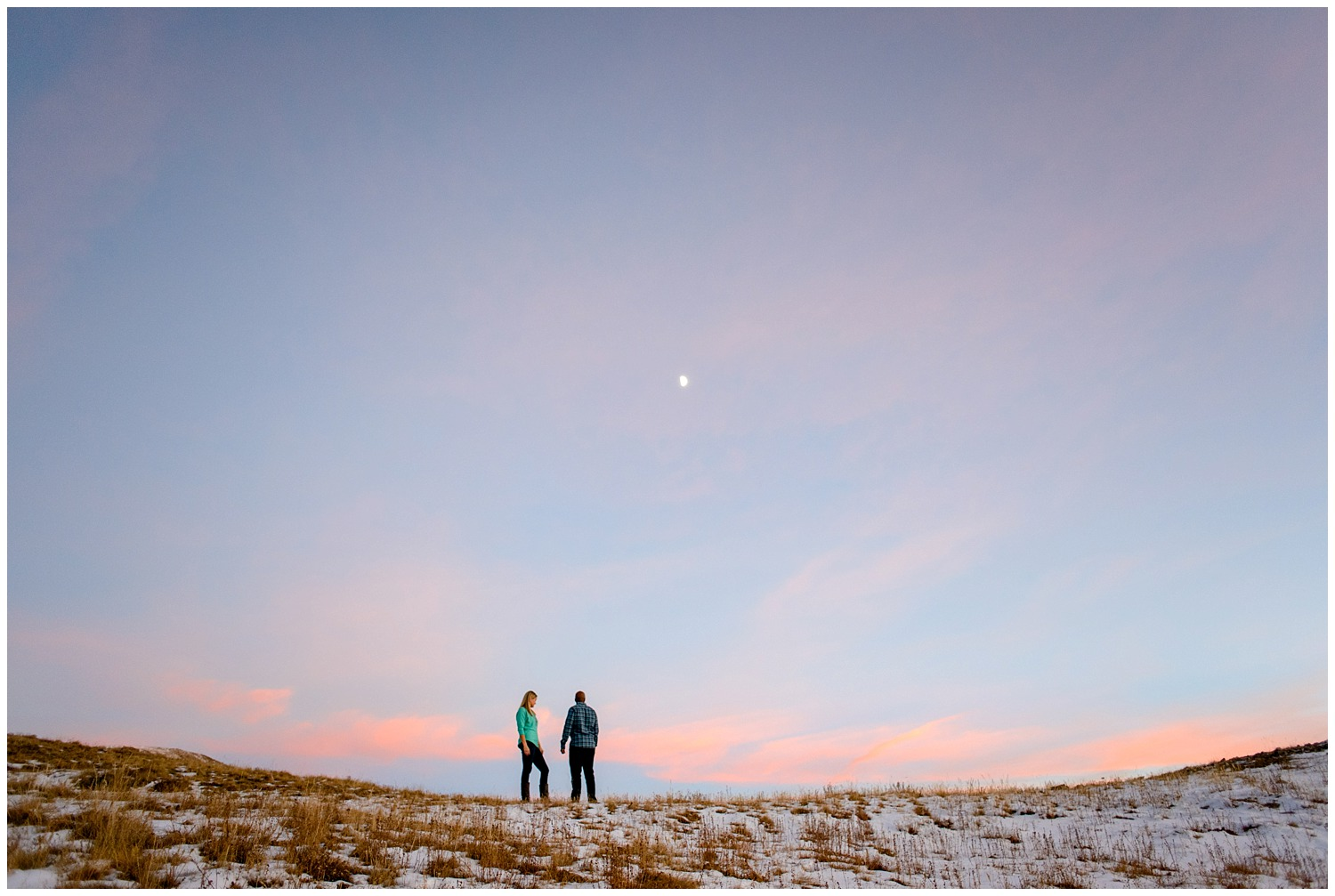 engaged couple on top of mountain with full moon