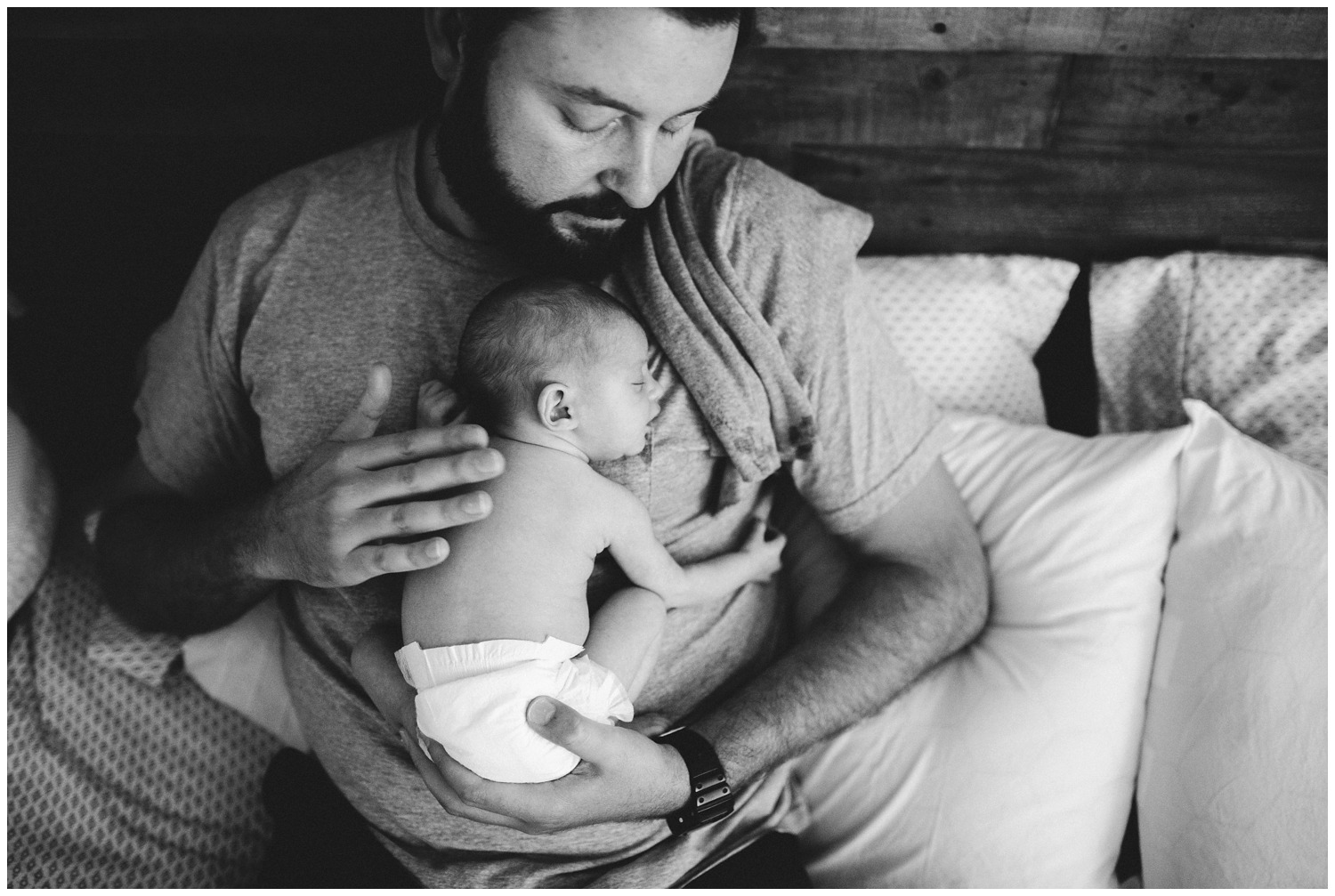 dad holds newborn in home