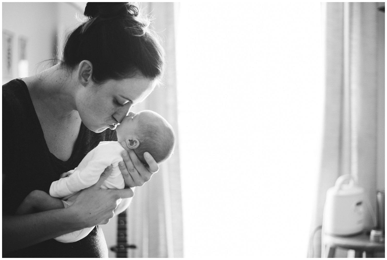 mom holds newborn in nursery