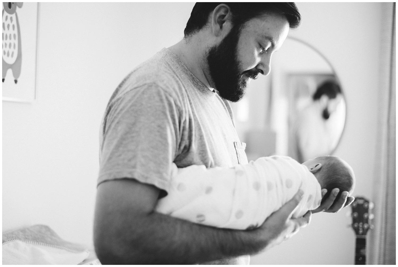 Dad holds newborn in Nursery
