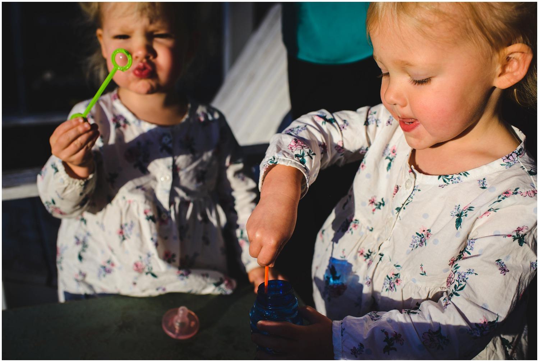 twins blowing bubbles in Colorado backyard