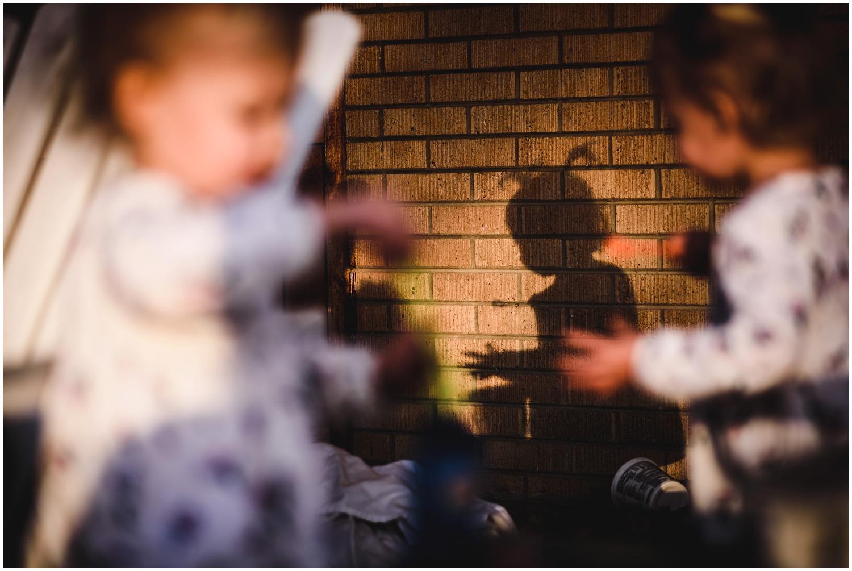 backyard shadow of twin girls in candid photo