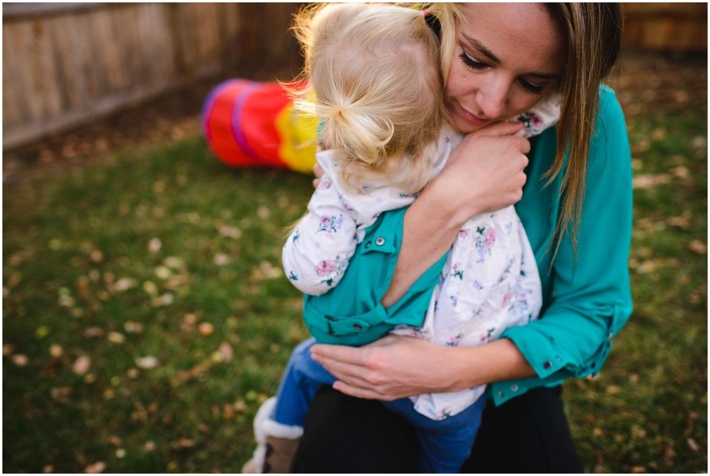 mom hugs daughter in backyard