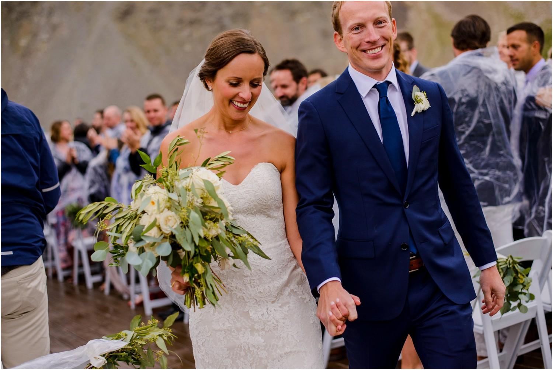 happy bride and groom walk down wedding aisle
