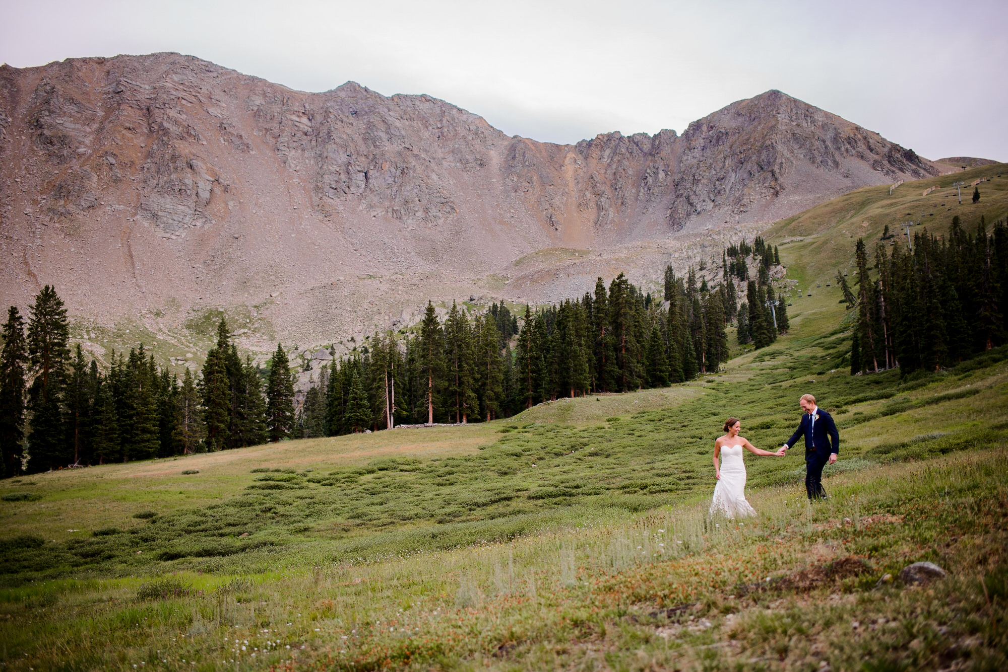 Copy of Bride and Groom walk on mountain at Arapahoe Basin