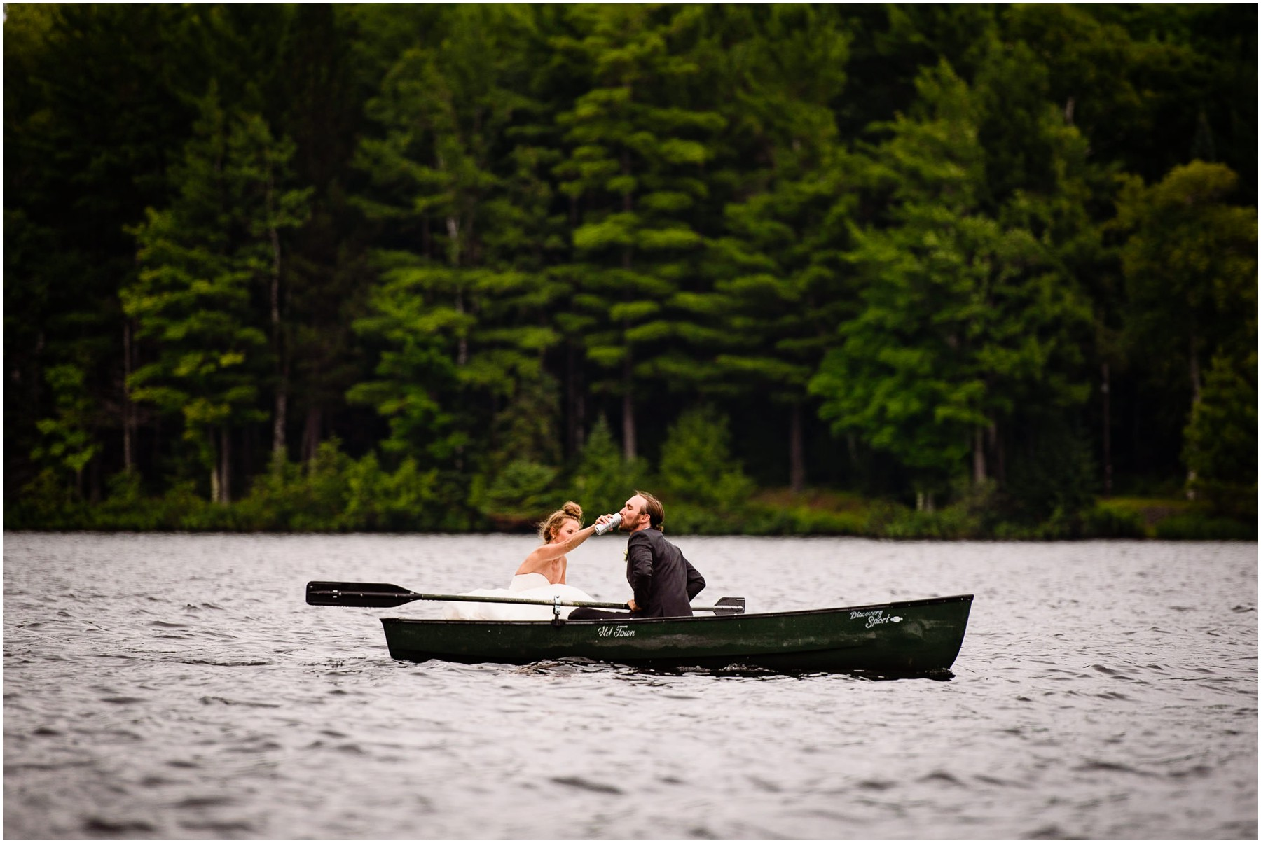 Bride gives Groom beer on Canoe in North Woods Wedding