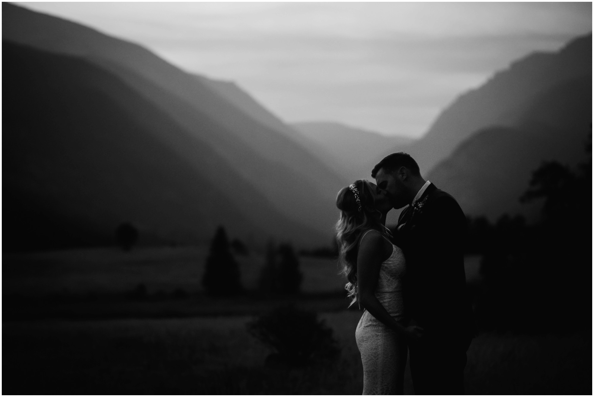 moody black and white photo of bride and groom kissing during colorado twilight