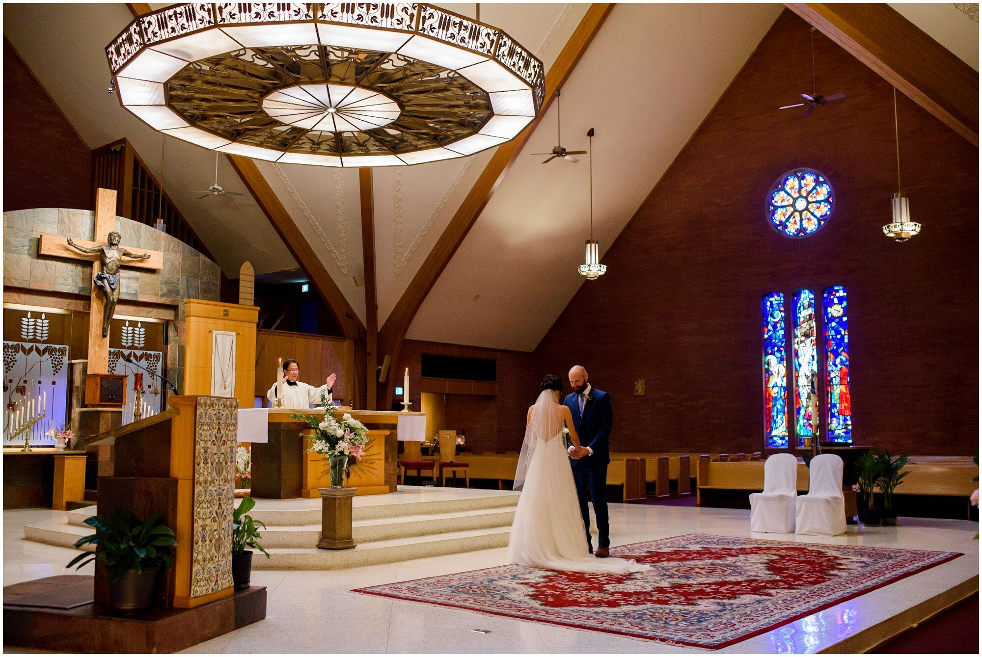 Bride and groom exchange vows in large cathedral in Boulder, Colorado