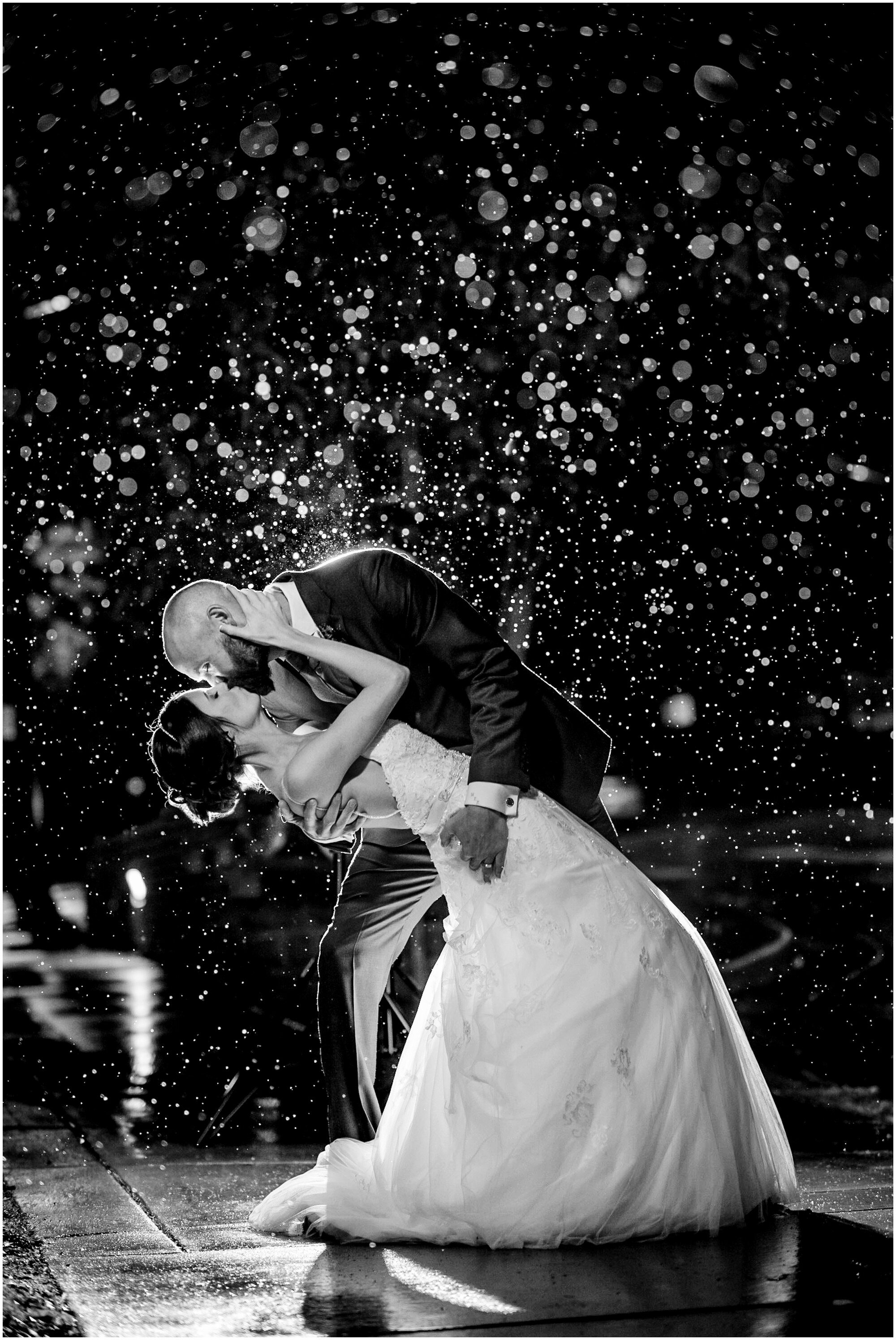 Bride and groom kiss on their wedding night in Boulder Colorado while the snow falls.