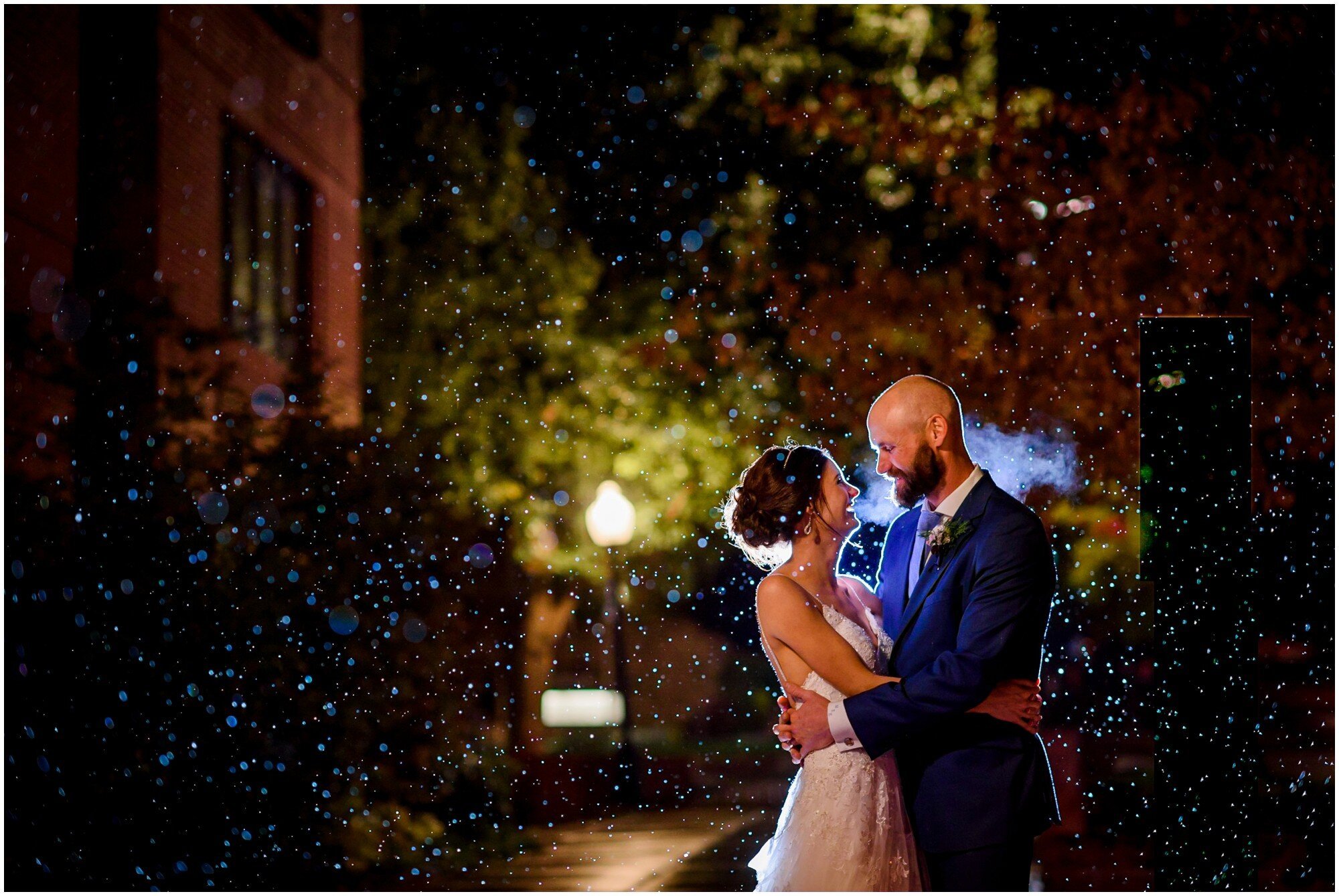 Wedding couple embraces in the snow after their wedding in Boulder, Colorado