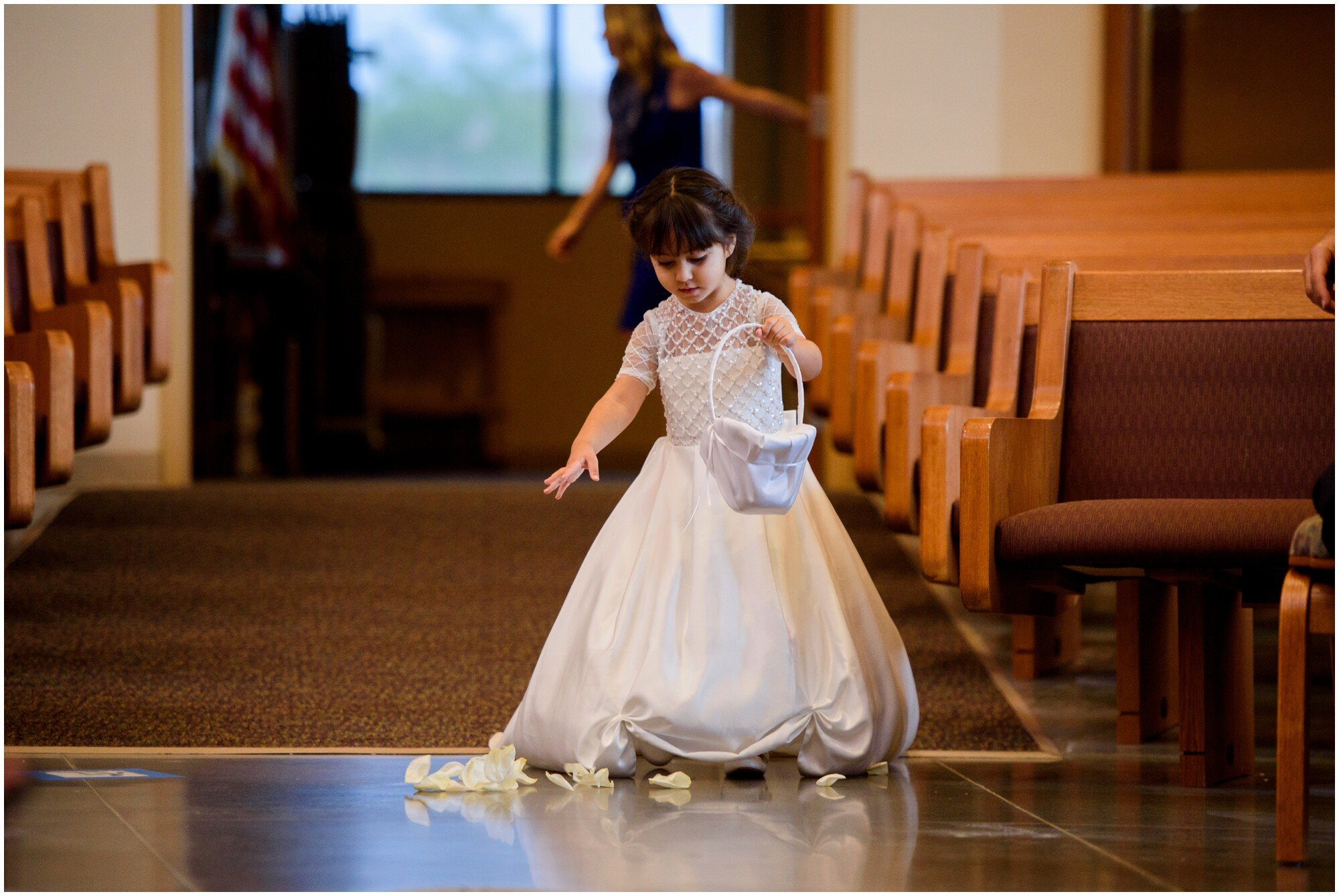 flower girl in beautiful dress walks down the aisle in highlands ranch