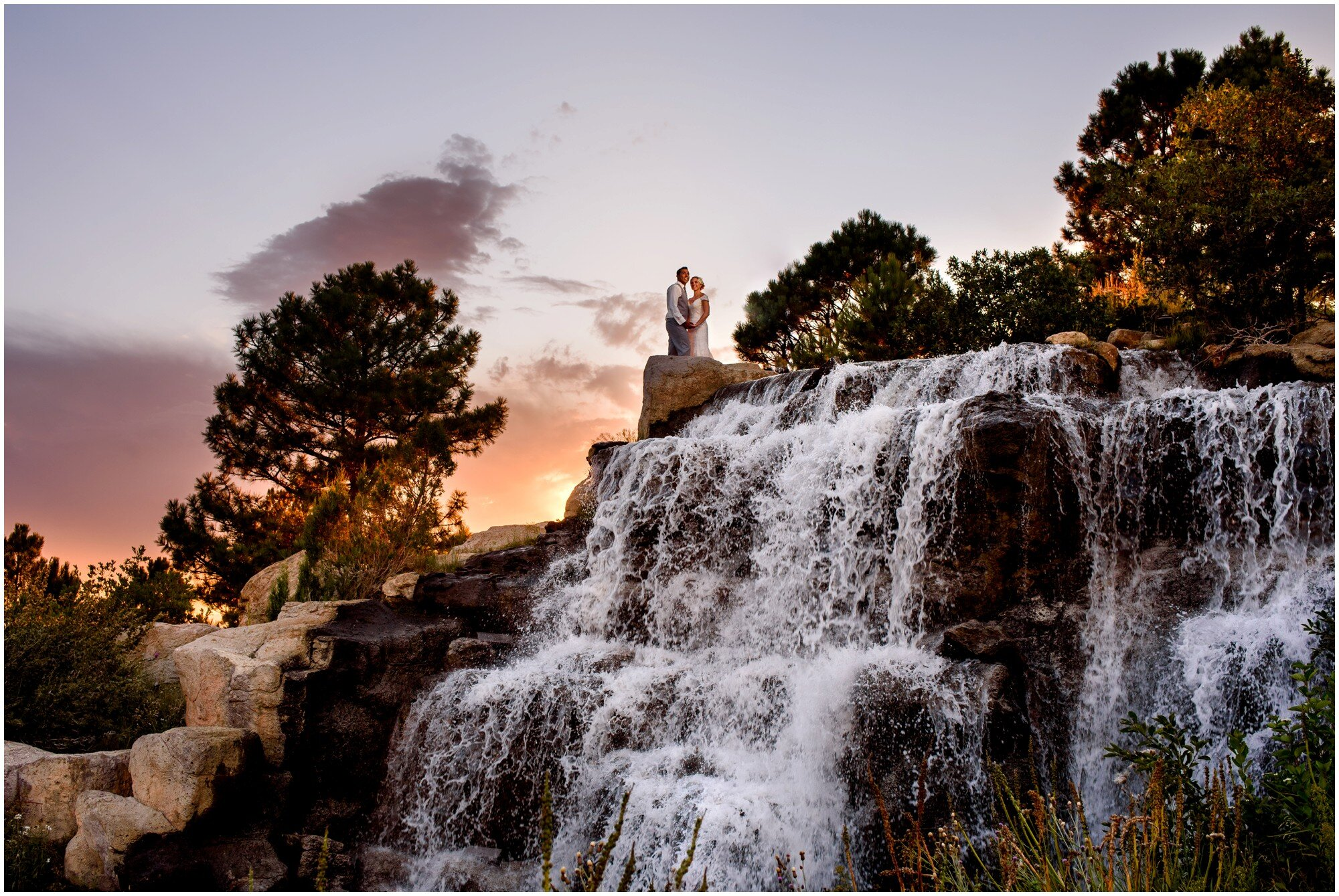 bride and groom on the waterfall at sanctuary golf course