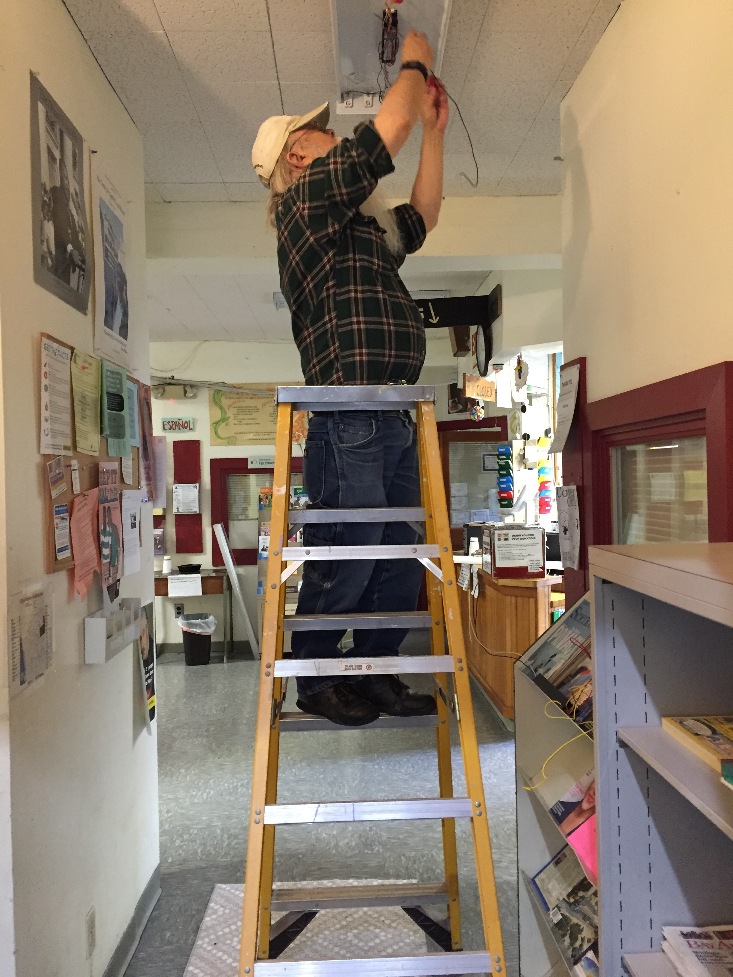 Long-time switchboard/IRC volunteer Tom K lends his skills to repair a light fixture before a shift