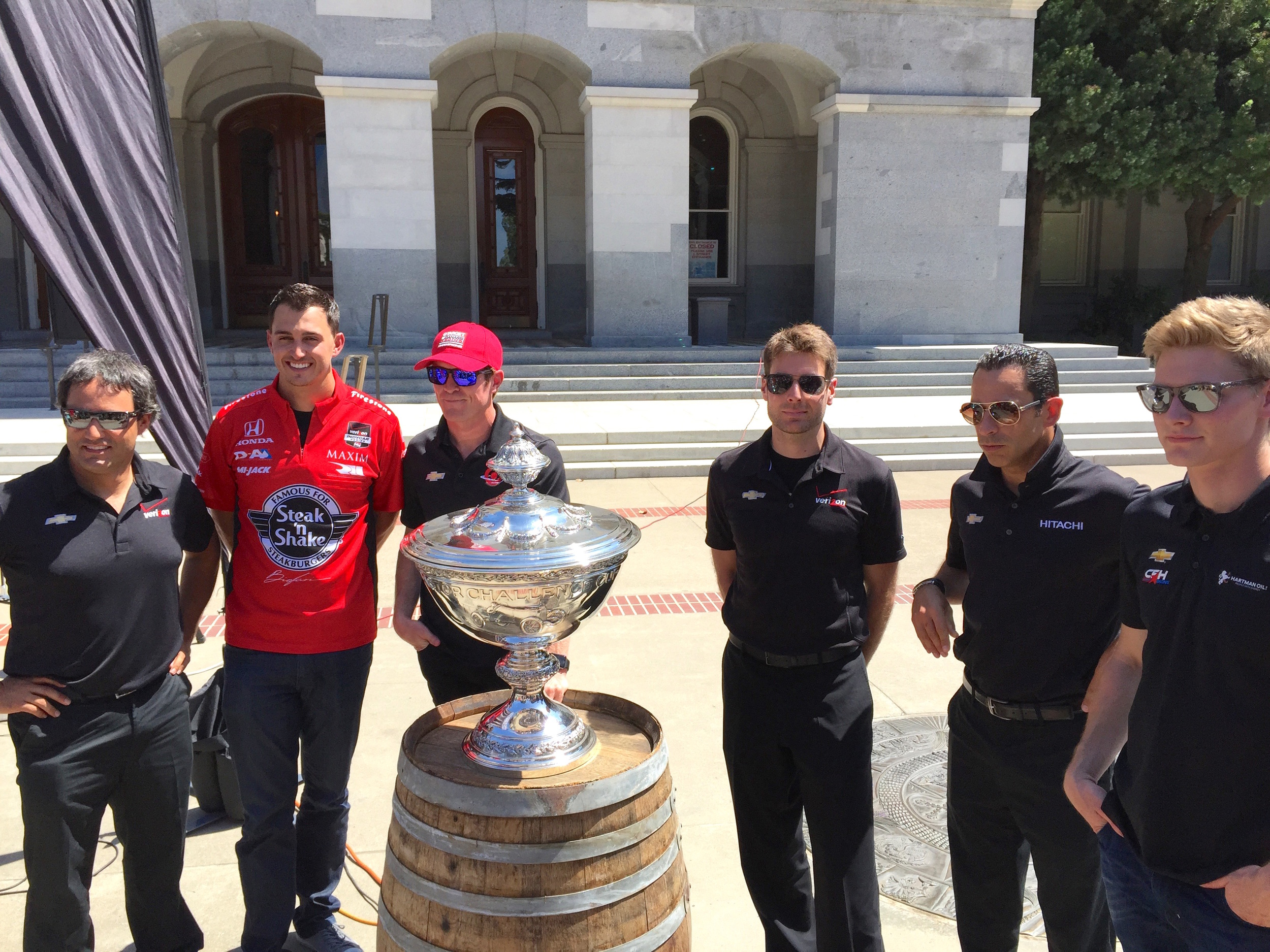 (From Left To Right) Juan Pablo Montoya, Graham Rahal, Scott Dixon, Will Power, Helio Castroneves, and Josef Newgarden stand behind the IndyCar Championship Trophy.