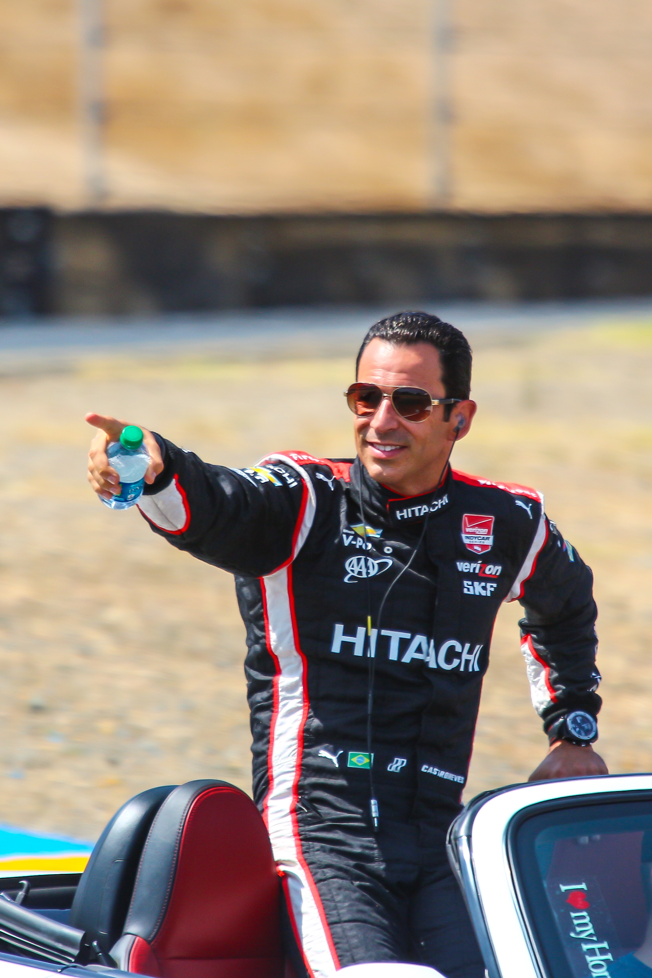 Helio Castroneves points to some cheering fans.