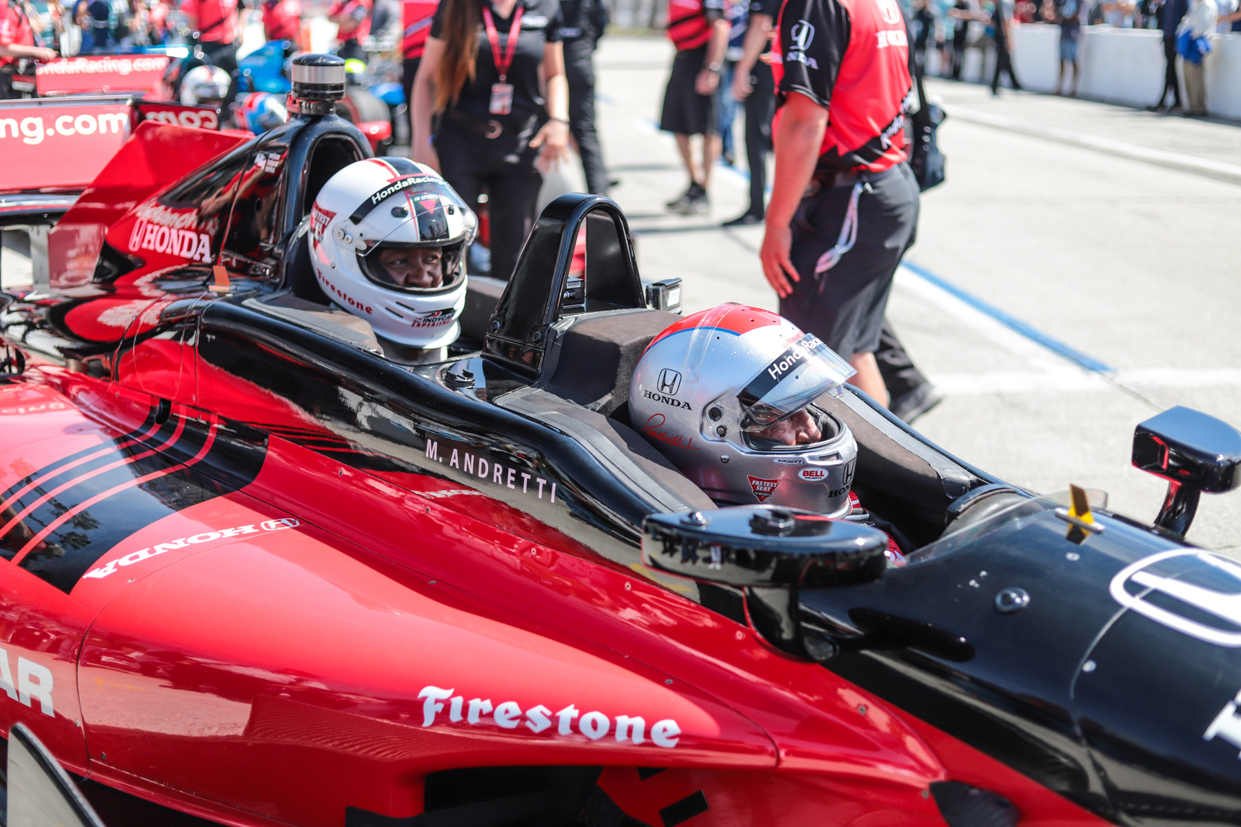 Mario Andretti prepares to take football player Willie McGinest around Long Beach in the IndyCar two-seater.