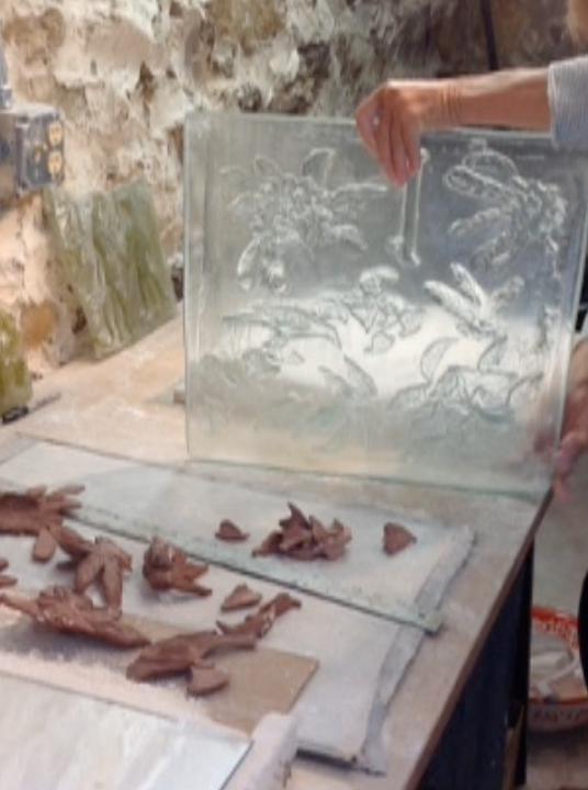 During firing the glass flows down into the pressed shapes.