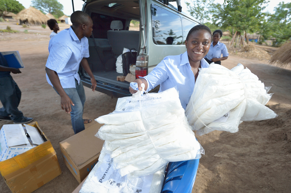 GRI staff in Uganda distributing mosquito nets during an outreach in the Rhino Refugee Camp area.