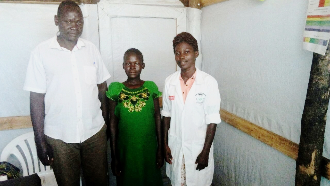 First-time mother, Rose (green dress), and Global Refuge staff at the Imvepi Health Center.