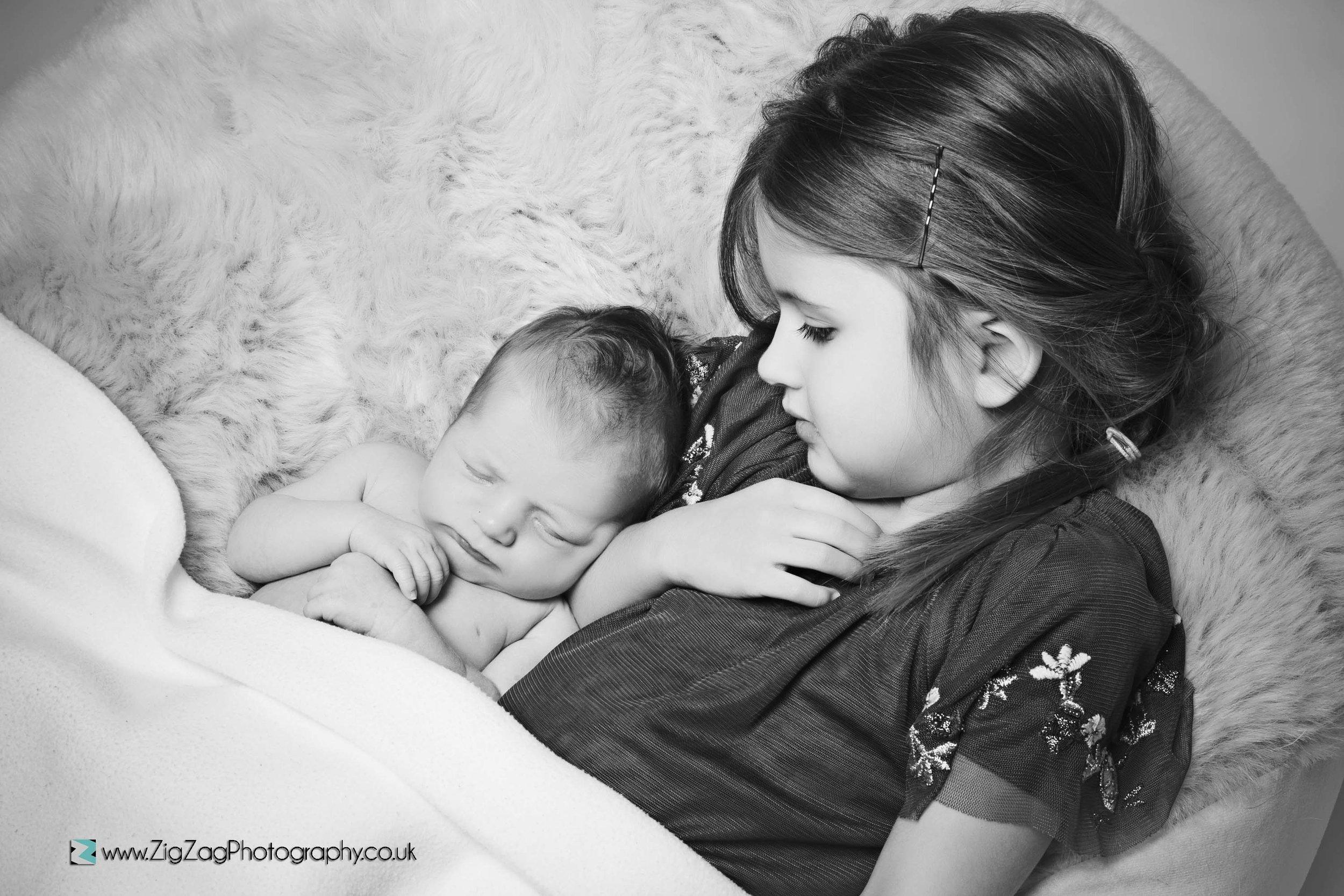 newborn-photography-photoshoot-leicester-studio-sibling-baby-black-white-sister-sleeping.jpg
