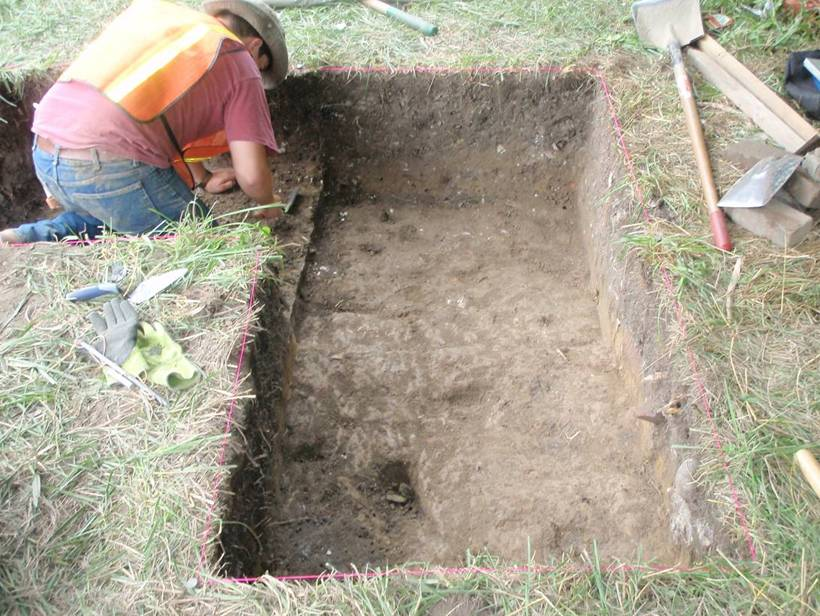 An archaeologist carefully excavates with a mason's trowel at 70 Broad Street.