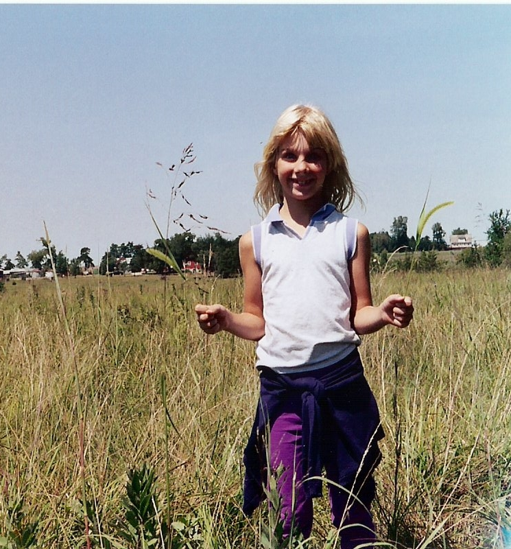 A younger me, demonstrating what grass looks like in one of our pastures