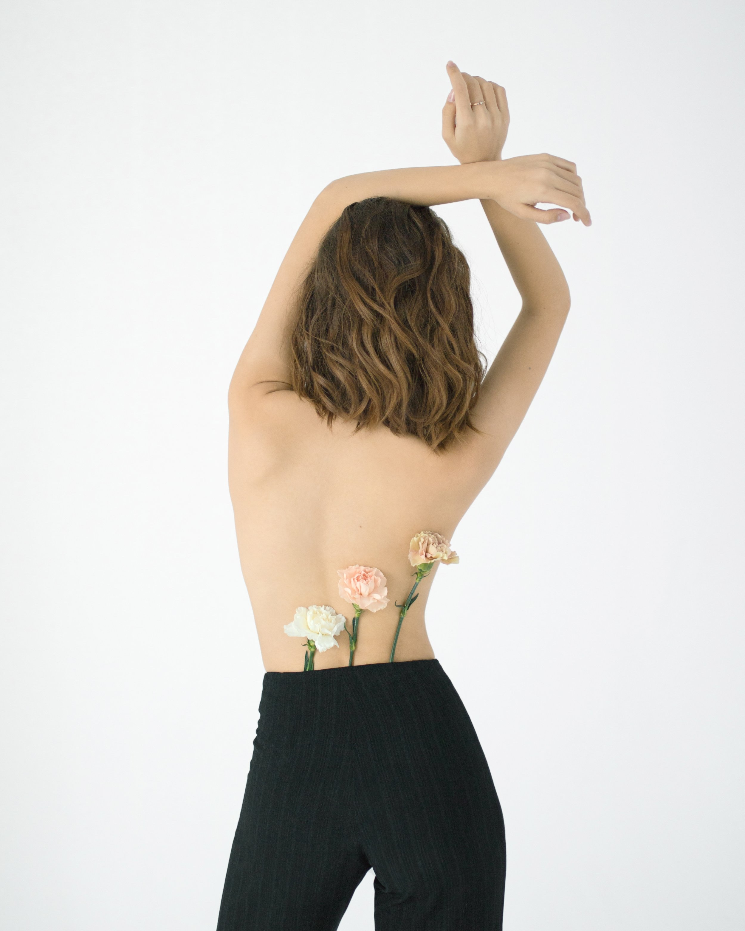 Original Human Skin Care - Image of a woman from behind with flowers tucked into the back pocket of her jeans.
